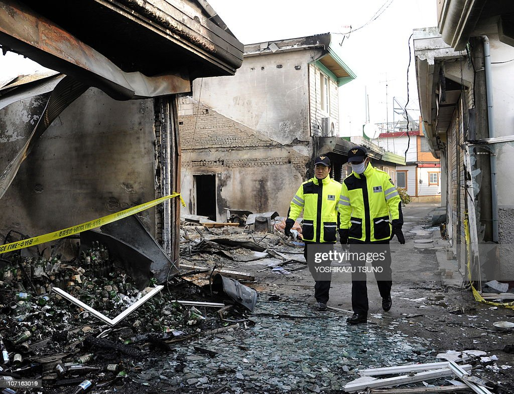 South Korean police officers patrol through an area badly damaged on Yeonpyeong island on November 27 four days after North Korea shelled the island...