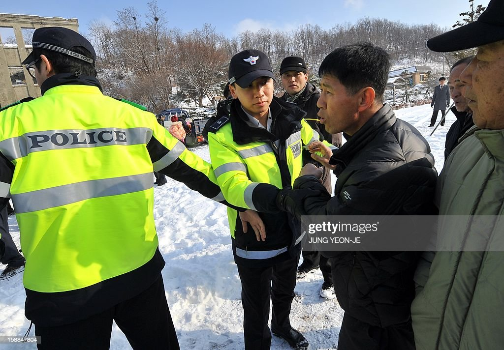 South Korean police try to separate local residents (R) who schuffled with activists after voicing fears of North Korean reprisals following the launch of anti-North Korea leaflets across the border in front of former North Korean Labor Party Cheorwon office building in the South Korean border county of Cheorwon on January 1, 2013. About 30 activists released seven balloons carrying 28,000 leaflets shouting 'Down with North Korea's dynastic dictorship!'.