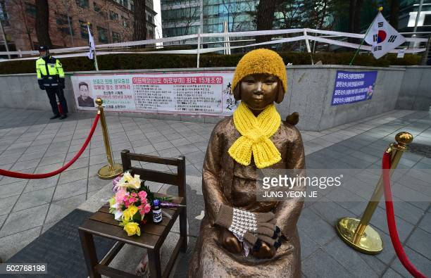 A South Korean policeman stands guard near a statue of a teenage girl in traditional costume called the 'peace monument' for former 'comfort women'...