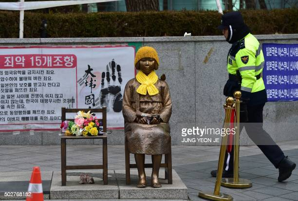 A South Korean policeman walks past a statue of a teenage girl in traditional costume called the 'peace monument' for former 'comfort women' who...