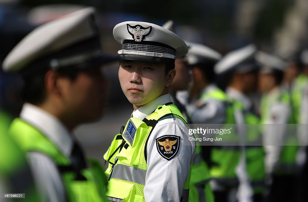 South Korean policemen stand guard during a May Day rally organized by the Korean Confederation of Trade Unions (KCTU) at the Seoul Railway Station on May 1, 2014 in Seoul, South Korea. South Korea's another biggest trade union, the Federation of Korean Trade Unions (FKTU) had announced cancellation of its annual May Day rally to mourn the ferry disaster victims.