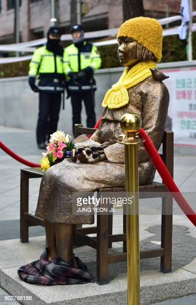 South Korean policemen stand guard near a statue of a teenage girl in traditional costume called the 'peace monument' for former 'comfort women' who...