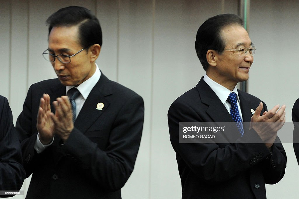 South Korean President Lee Myung-Bak (L) and Chinese Premier Wen Jiabao (R) applaud during the during the Association of Southeast Asian Nations (ASEAN) plus three commemorative summit in Phnom Penh on November 19, 2012 following the 21st ASEAN Leaders Summit. Southeast Asian nations were to press China to quickly begin talks on easing tensions over maritime territorial rows that have shaken the region and overshadowed efforts to boost trade. AFP PHOTO / ROMEO GACAD