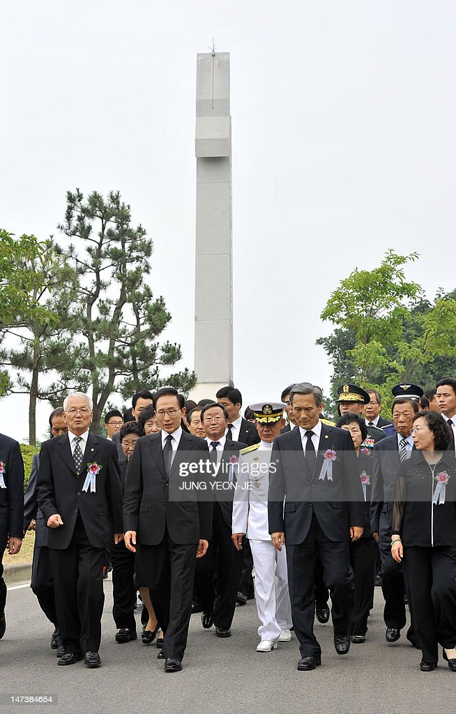 South Korean President Lee Myung-Bak (L from center) and Defence Minister Kim Kwan-Jin (R from center) walk past a monument (back) of the second naval battle of Yeonpyeong during the 10th anniversary commemorative ceremony of the second naval battle of Yeonpyeong at the Navy's 2nd Fleet Command in Pyeongtaek, about 70 kilometers south of Seoul, on June 29, 2012. The battle erupted on June 29, 2002, when two of the North's patrol boats crossed the disputed Yellow Sea border. Six South Korean sailors were killed and 18 injured while an estimated 13 North Koreans died.