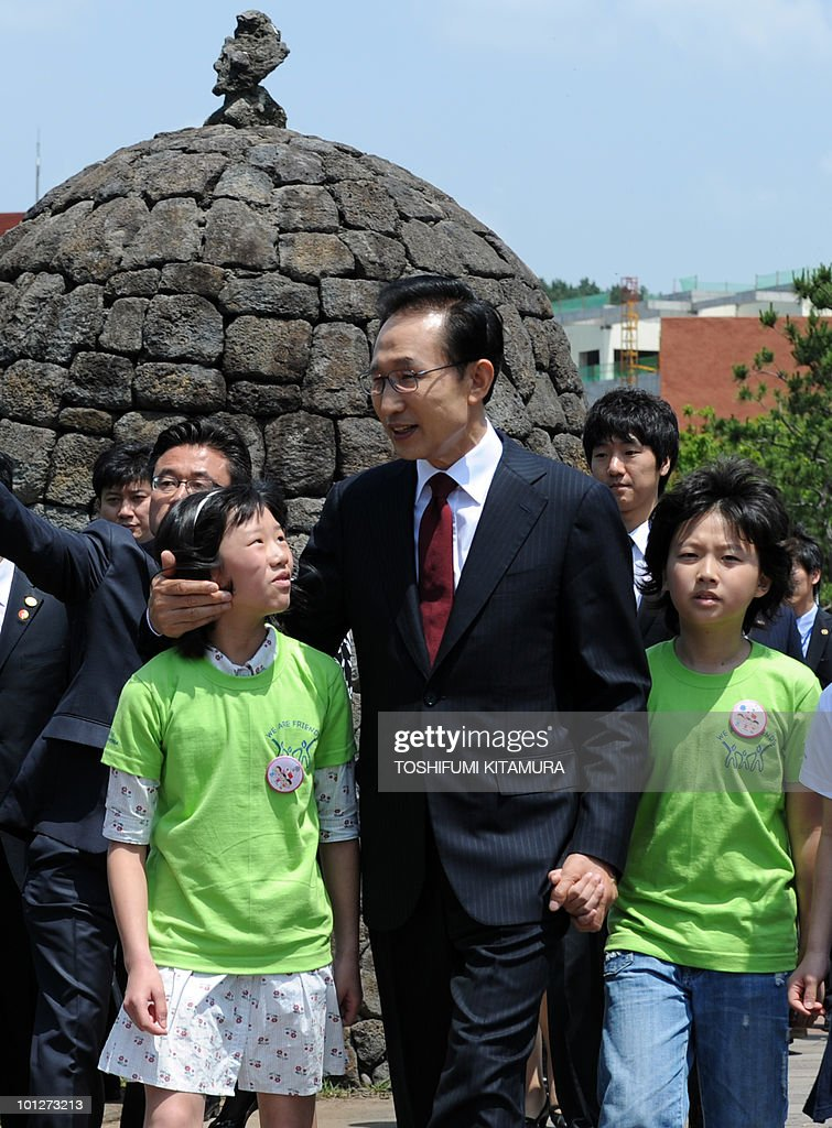 South Korean President Lee Myung-Bak (C) talks with school children as he enters the site for a time capsule laying ceremony in Seogwipo on May 30, 2010, the second-day of trilateral summit meetings. The trilateral summit meetings with the Chinese and Japanese leaders discussed the sinking of the South Korean warship, Cheonan, which claimed 46 lives and is blamed on North Korea. The Chinese premier said May 30 there is an 'urgent' need to avoid clashes and ease tensions following the sinking.