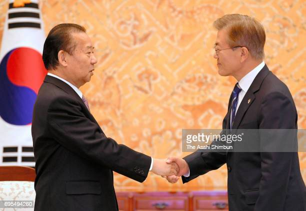 South Korean President Moon JaeIn and Japan's ruling Liberal Democratic Party secretary general Toshihiro Nikai shake hands prior to their meeting on...