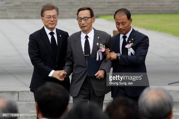 South Korean President Moon Jaein helps a Korean War veteran Park YongGyu during a ceremony marking Korean Memorial Day at the Seoul National...