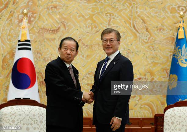 South Korean President Moon Jaein shakes hands with Toshihiro Nikai Secretary General of the Japanese Liberal Democratic Party during their meeting...