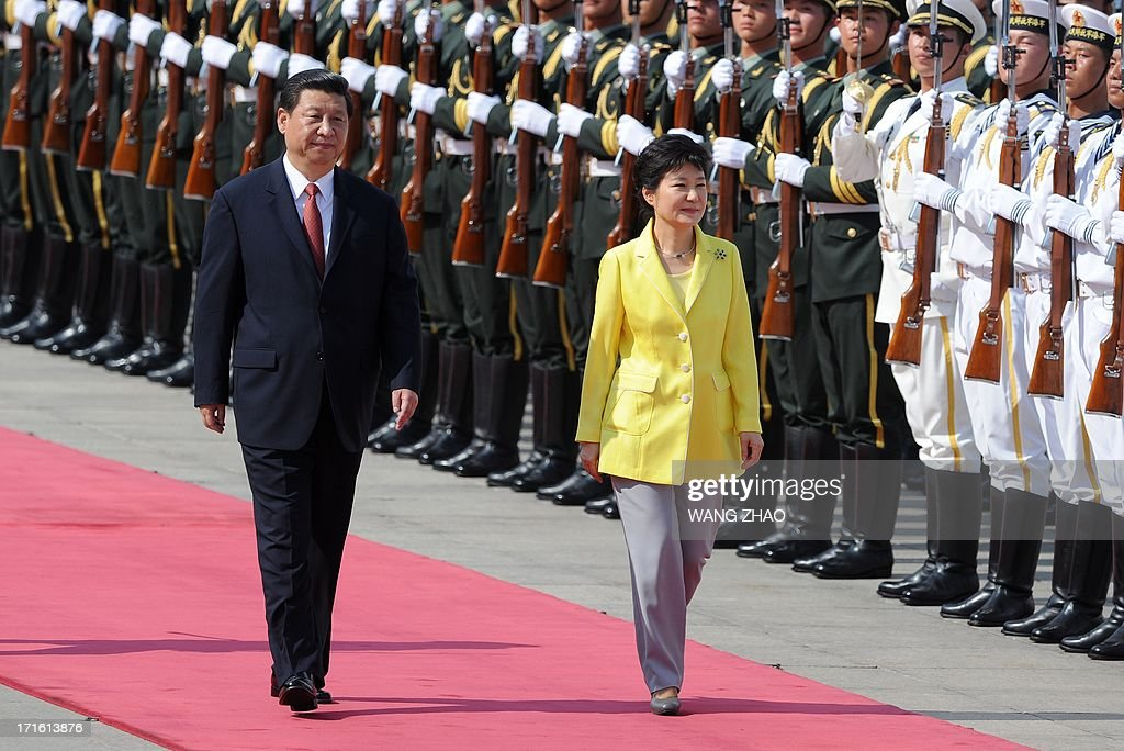 South Korean President Park Geun-Hye (R) and Chinese President Xi Jinping (L) inspect Chinese honour guards during a welcoming ceremony outside the Great Hall of the People in Beijing on June 27, 2013. Park Geun-Hye is on a visit to China from June 27 to 30. AFP PHOTO / POOL / WANG ZHAO