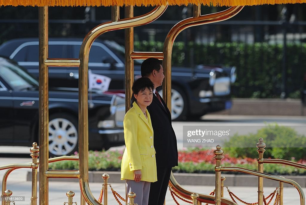 South Korean President Park Geun-Hye (L) and Chinese President Xi Jinping (R) prepare to inspect Chinese honour guards during a welcoming ceremony outside the Great Hall of the People in Beijing on June 27, 2013. Park Geun-Hye is on a visit to China from June 27 to 30.