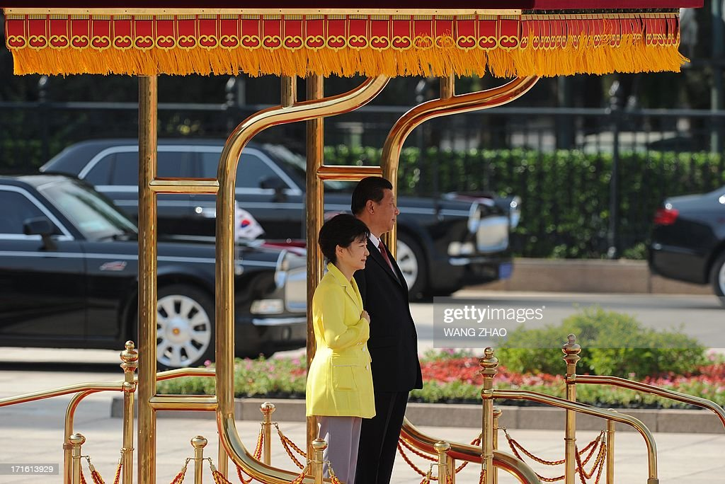 South Korean President Park Geun-Hye (L) and Chinese President Xi Jinping (R) prepare to inspect Chinese honour guards during a welcoming ceremony outside the Great Hall of the People in Beijing on June 27, 2013. Park Geun-Hye is on a visit to China from June 27 to 30. AFP PHOTO / POOL / WANG ZHAO