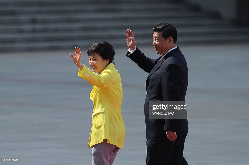 South Korean President Park Geun-Hye (L) and Chinese President Xi Jinping (R) wave during a welcoming ceremony outside the Great Hall of the People in Beijing on June 27, 2013. Park Geun-Hye is on a visit to China from June 27 to 30.