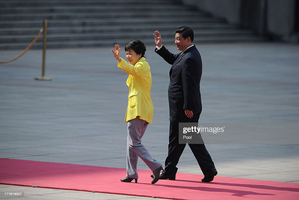 South Korean President Park Geun-Hye (L) and Chinese President Xi Jinping wave as they inspect Chinese honour guards during a welcoming ceremony outside the Great Hall of the People on June 27, 2013 in Beijing, China. Park Geun-Hye is visiting China from June 27 to 30.