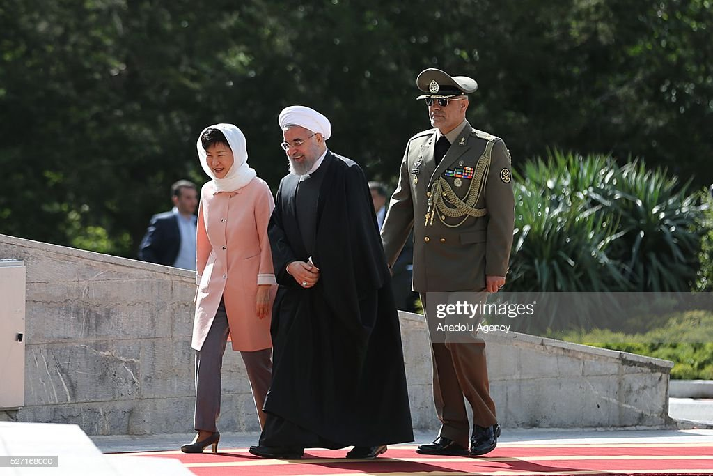South Korean President Park Geun-Hye (L) and Iran's President Hassan Rouhani (C) walk past the honor guards during an official welcoming ceremony at Sadabad Palace in Tehran, Iran on May 2, 2016.