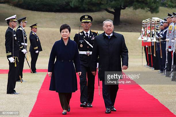 South Korean President Park GeunHye and Kazakhstan President Nursultan Nazarbayev walk towards a guard of honour during a welcoming ceremony at the...