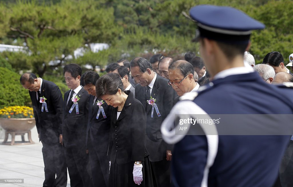 South Korean President Park Geun-Hye (C) bows during a ceremony marking Korean Memorial Day at the National Cemetery in Seoul on June 6, 2013. South Korea marked the 58th anniversary of the Memorial Day for those killed in the 1950-53 Korean War. Park urged North Korea to accept her administration's 'trust building' policy initiative that could open a new era of peace and hope on the peninsula.