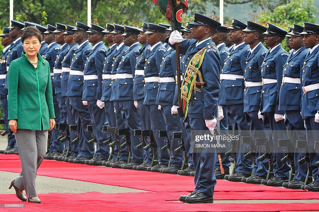 South Korean President Park Geun-hye (L) inspects a guard of honour upon her arrival at the StateHouse in Nairobi, during the first state visit by a South Korean president to the country in 34 years. / AFP / SIMON