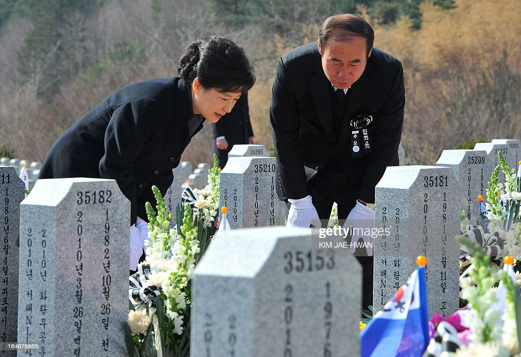 South Korean President Park Geun-Hye (L) pays homage to the sailors who died in 2010 when the naval vessel 'Cheonan' was sunk, during a ceremony at a cemetery in the central city of Daejeon on March 26, 2013. Forty-six sailors died after the naval vessel Cheonan was sunk by what Seoul insists was a North Korean submarine. Addressing a ceremony for the 46 sailors, South Korean President Park Geun-Hye warned Pyongyang that its only 'path to survival' lay in abandoning its nuclear and missile programs. AFP PHOTO / POOL/ KIM JAE-HWAN