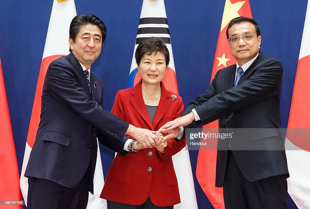 South Korean President Park Geun-Hye (C) poses with Japanese Prime Minister Shinzo Abe (L) and Chinese Premier Li Keqiang (R) as they meet to hold a trilateral summit at the presidential Blue House on November 1, 2015 in Seoul, South Korea. President Park Geun-hye, Japanese Prime Minister Shinzo Abe and Chinese Premier Li Keqiang gathered in Seoul to hold a trilateral summit for the first time in three years. The issues to be discussed include the trilateral free trade agreement, perceptions on wartime history, and territorial disputes.