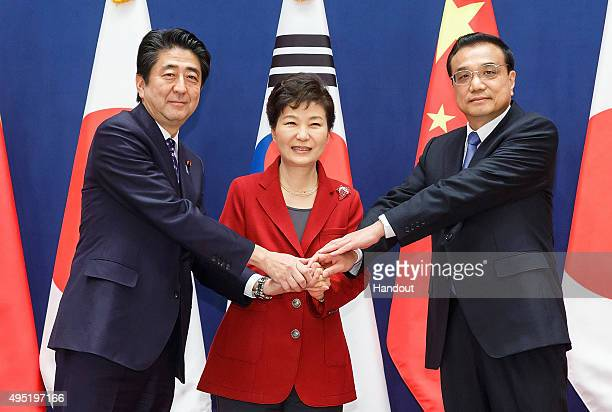 South Korean President Park GeunHye poses with Japanese Prime Minister Shinzo Abe and Chinese Premier Li Keqiang as they meet to hold a trilateral...