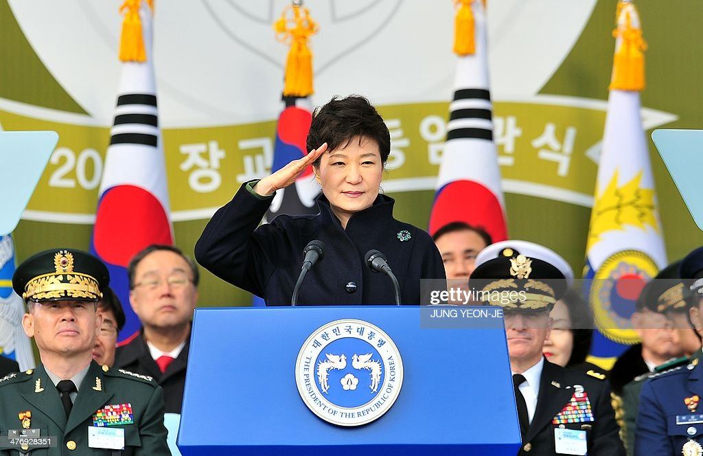 South Korean President Park Geun-Hye (C) salutes during the joint commission ceremony of 5,860 new military officers of the army, navy, air force and marines at the military headquarters in Gyeryong, south of Seoul, on March 6, 2014. Park urged North Korea to give up its nuclear program, saying denuclearization will pave the way for greater economic cooperation and ultimately unification between the two divided states.