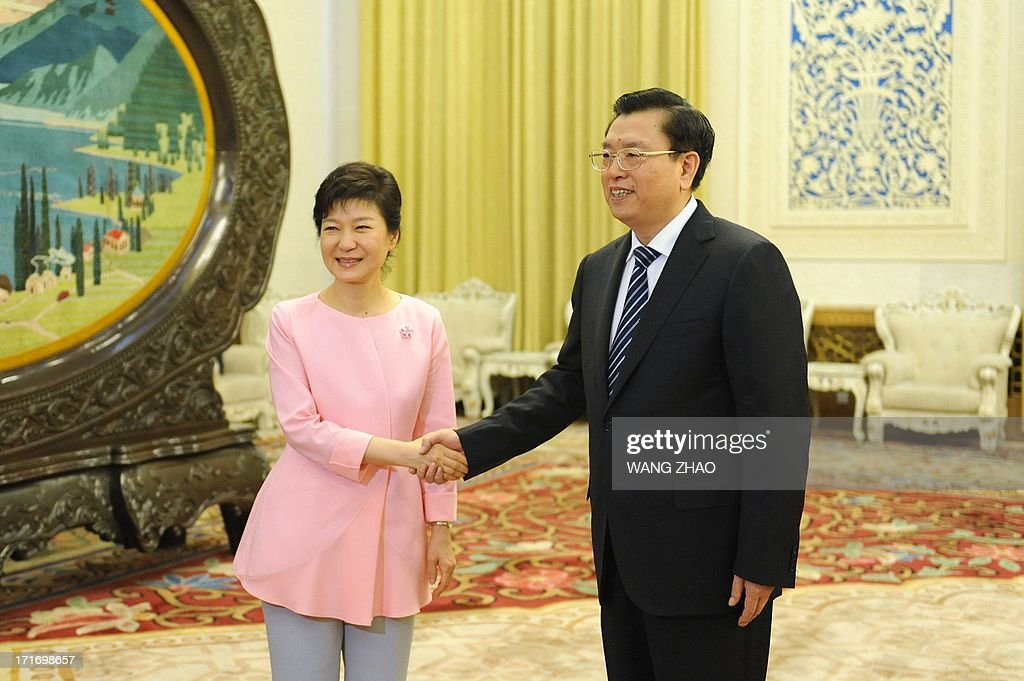 South Korean President Park Geun-Hye (L) shakes hands with Chinese Chairman of the National People's Congress Zhang Dejiang (R) at the Great Hall of the People in Beijing on June 28, 2013. Park Geun-Hye is on a visit to China from June 27 to 30. AFP PHOTO / POOL / WANG ZHAO