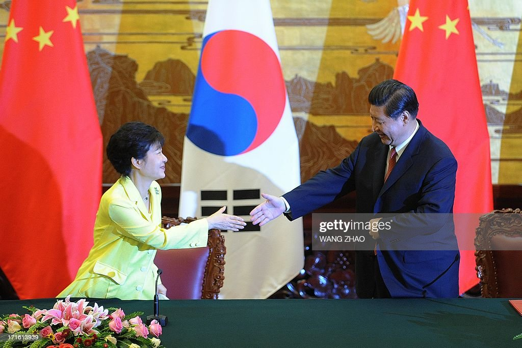 South Korean President Park Geun-Hye (L) shakes hands with Chinese President Xi Jinping (R) after a joint declaration ceremony at the Great Hall of the People in Beijing on June 27, 2013. Park Geun-Hye is on a visit to China from June 27 to 30.