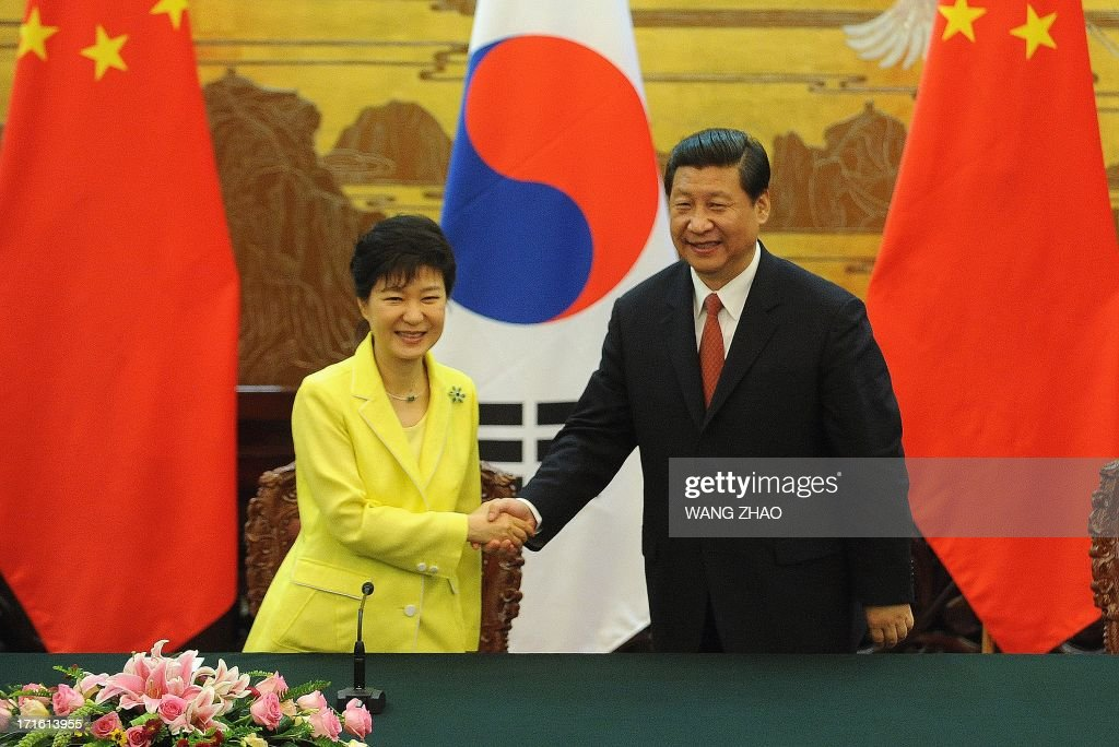 South Korean President Park Geun-Hye (L) shakes hands with Chinese President Xi Jinping (R) after a joint declaration ceremony at the Great Hall of the People in Beijing on June 27, 2013. Park Geun-Hye is on a visit to China from June 27 to 30. AFP PHOTO / POOL / WANG ZHAO