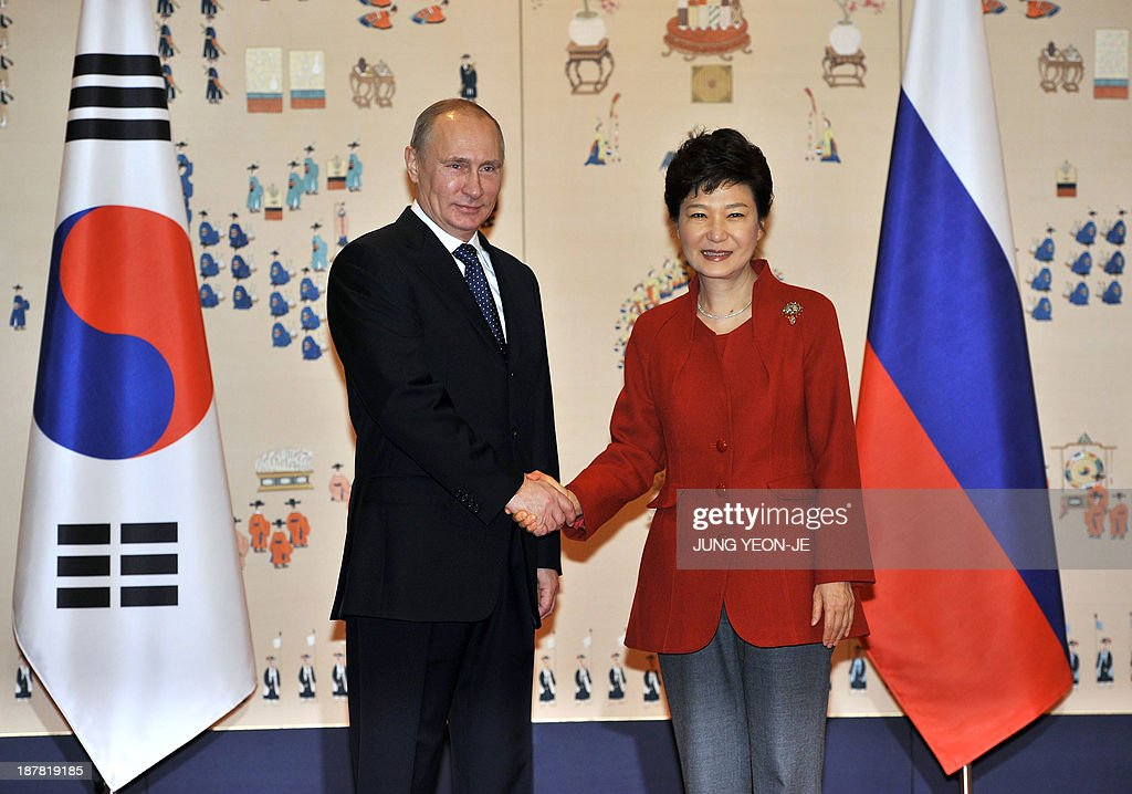 South Korean President Park Geun-Hye (R) shakes hands with Russian President Vladimir Putin (L) at the presidential Blue House in Seoul on November 13, 2013. Russian President Vladimir Putin was in South Korea on November 13 to push a pet project for a new major trading route linking Asia and Europe by rail that requires prying open North Korea.