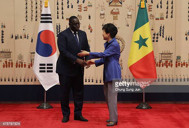 South Korean President Park GeunHye shakes hands with Senegal President Macky Sall prior to their meeting at the presidential blue house on June 4...