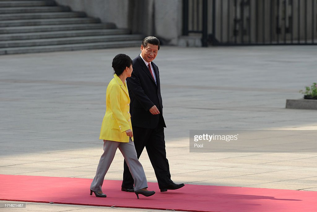 South Korean President Park Geun-Hye (L) talks with Chinese President <a gi-track='captionPersonalityLinkClicked' href=/galleries/search?phrase=Xi+Jinping&family=editorial&specificpeople=2598986 ng-click='$event.stopPropagation()'>Xi Jinping</a> as they prepare to inspect Chinese President <a gi-track='captionPersonalityLinkClicked' href=/galleries/search?phrase=Xi+Jinping&family=editorial&specificpeople=2598986 ng-click='$event.stopPropagation()'>Xi Jinping</a> inspect Chinese honour guards during a welcoming ceremony outside the Great Hall of the People on June 27, 2013 in Beijing, China. Park Geun-Hye is visiting China from June 27 to 30.
