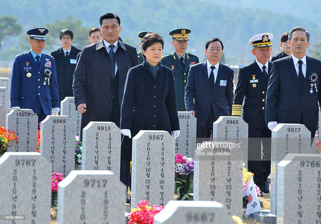 South Korean President Park Geun-Hye (C) walks past headstones at a cemetery to pay homage to the sailors who died when the naval vessel 'Cheonan' was sunk in 2010, during a ceremony in the central city of Daejeon on March 26, 2013. Forty-six sailors died after the naval vessel Cheonan was sunk by what Seoul insists was a North Korean submarine. Addressing a ceremony for the 46 sailors, South Korean President Park Geun-Hye warned Pyongyang that its only 'path to survival' lay in abandoning its nuclear and missile programs. AFP PHOTO / POOL/ KIM JAE-HWAN