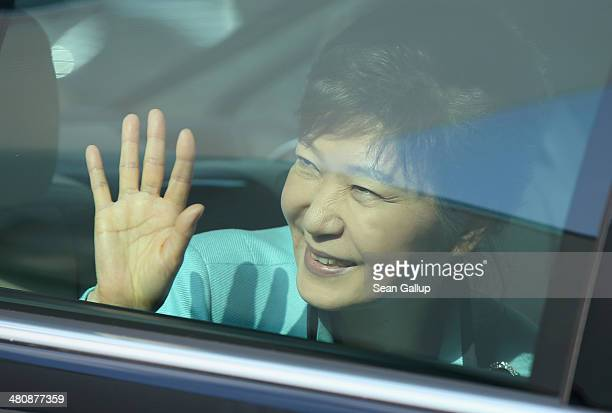 South Korean President Park Geunhye waves from her car as she departs after visiting the Siemens gas turbine factory on March 27 2014 in Berlin...