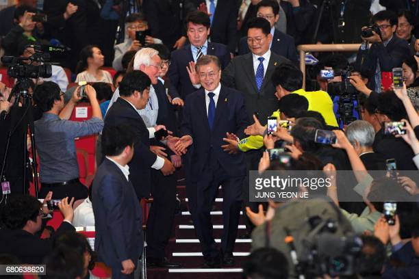 South Korean presidential candidate Moon Jaein of the Democratic Party greets party members as he arrives to watch a broadcast of exit poll results...