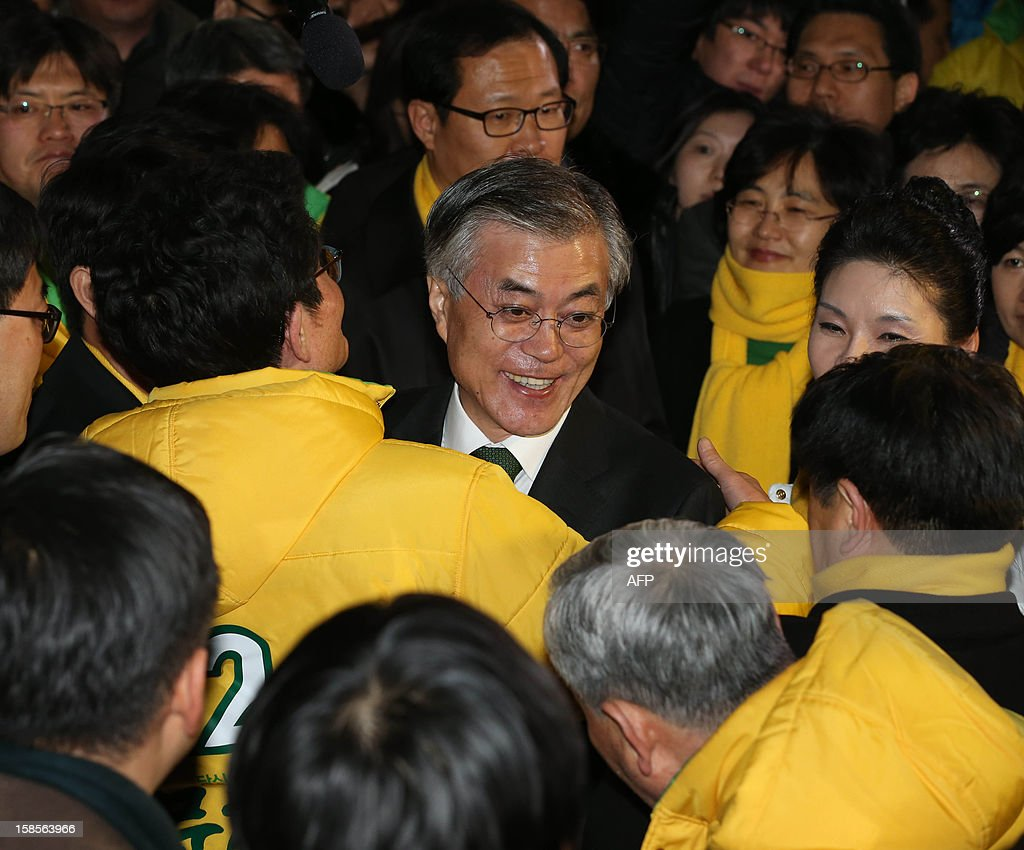 South Korean presidential candidate Moon Jae-In (C) of the main opposition Democratic United Party is greeted by supporters after a news conference declaring his rival's victory at the party headquarters in Seoul on December 19, 2012. South Korea elected its first female president on December 19, handing a slim but historic victory to conservative ruling party candidate Park Geun-Hye, daughter of the country's former military ruler. ILBO