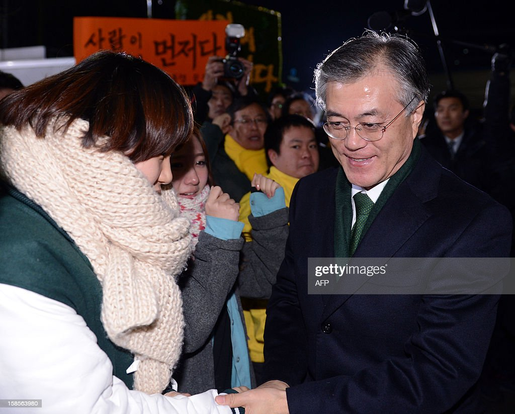 South Korean presidential candidate Moon Jae-In (R) of the main opposition Democratic United Party is greeted by supporters after a news conference declaring his rival's victory at the party headquarters in Seoul on December 19, 2012. South Korea elected its first female president on December 19, handing a slim but historic victory to conservative ruling party candidate Park Geun-Hye, daughter of the country's former military ruler. ILBO