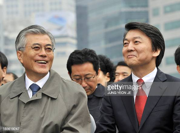 South Korean presidential candidates Moon JaeIn of the main opposition Democratic United Party and independent hopeful Ahn CheolSoo smile as they...