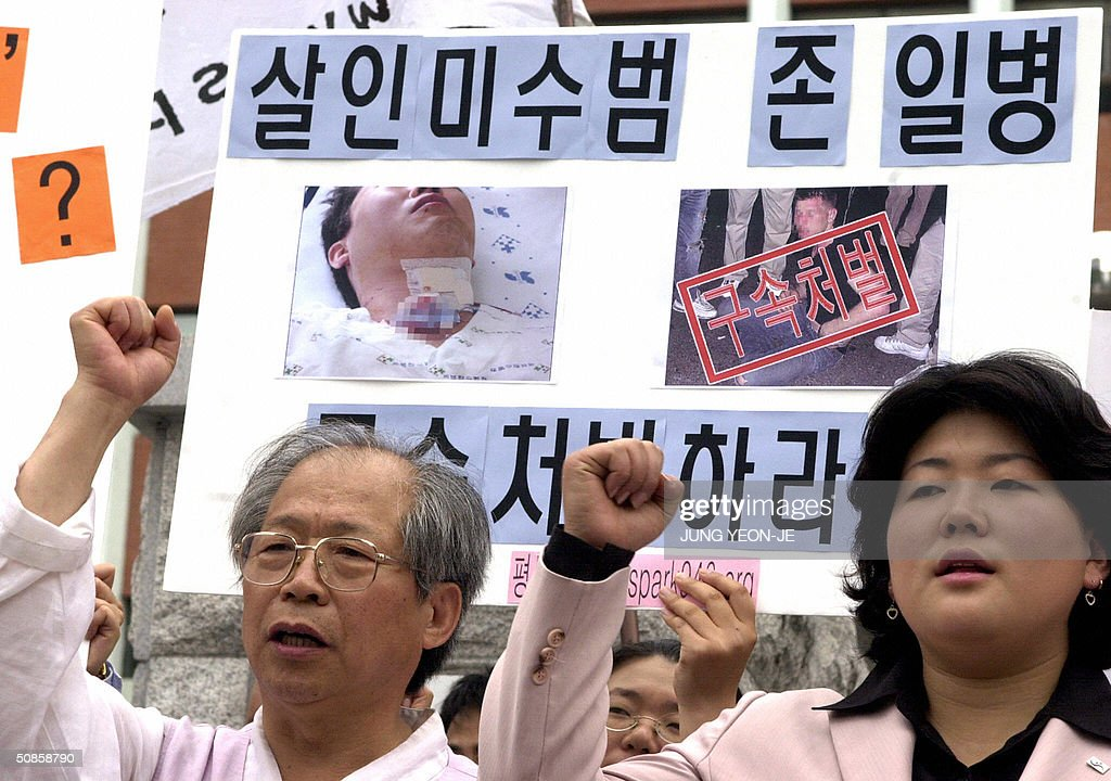A South Korean protester holds placard reading 'Unequal SOFA between Korea and America' during a protest rally in front of a police station in Seoul, 20 May 2004 after a US soldier was suspected of stabbing a South Korean citizen.