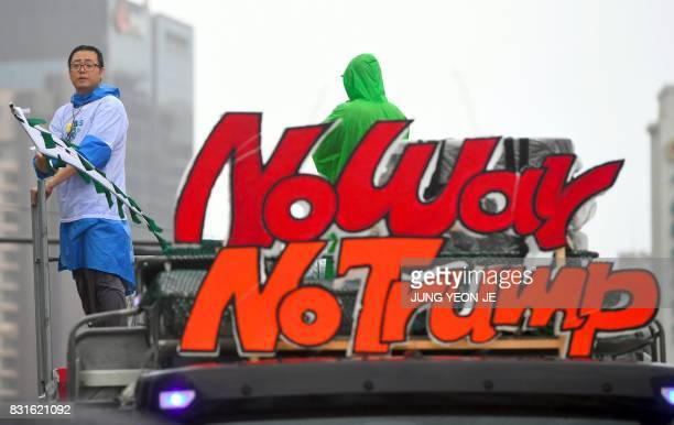 A South Korean protester waves a flag on the top of a truck decorated with words reading 'No War No Trump' as protesters march towards the US embassy...
