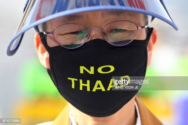 A South Korean protester wears a face mask reading 'No THAAD' during a rally against the deployment of the US Terminal High Altitude Area Defense...