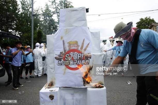 South Korean protesters burn an effigy symbolizing the United States with an illustration of US President Donald Trump during a rally against the...