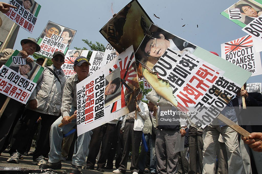 South Korean protesters burn placards carrying the images of Japanese Prime Minister Shinzo Abe and Osaka Mayor Toru Hashimoto during a rally on May 23, 2013 in Seoul, South Korea. Recent remarks by the mayor of Osaka on the historic perception of 'comfort women', conscripted by Japanese military brothels during World War II, have recieved intense criticism from neigbouring countries and the US.