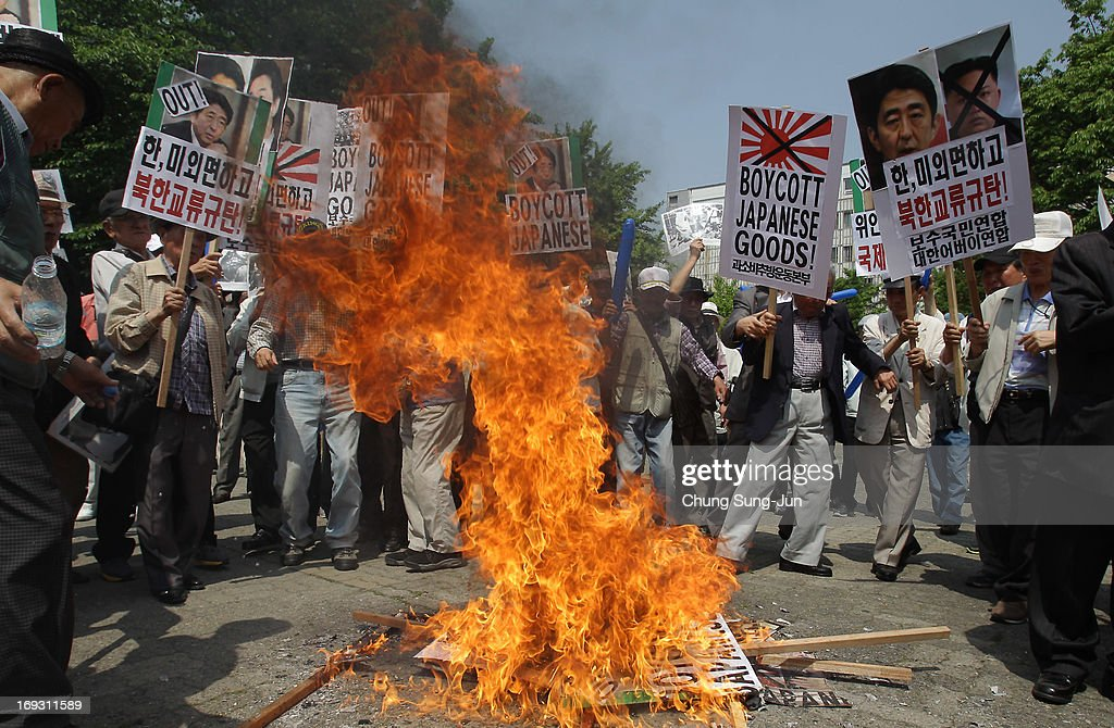 South Korean protesters burn portraits of Japanese Prime Minister Shinzo Abe and Osaka Mayor Toru Hashimo during a rally on May 23, 2013 in Seoul, South Korea. Recent remarks by the mayor of Osaka on the historic perception of 'comfort women', conscripted by Japanese military brothels during World War II, have recieved intense criticism from neigbouring countries and the US.