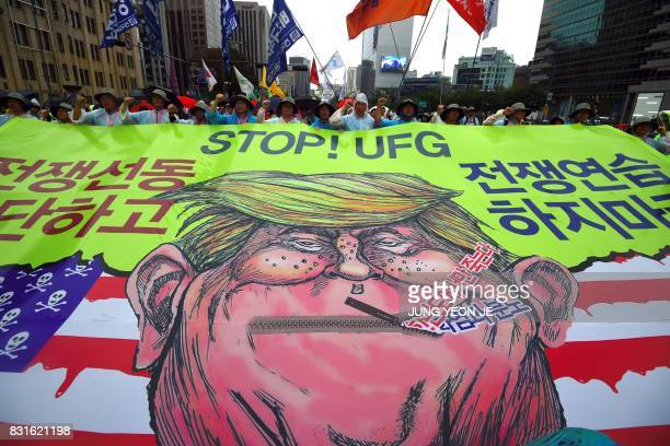 TOPSHOT South Korean protesters carry a banner showing a caricature of US President Donald Trump as they march towards the US embassy during an...