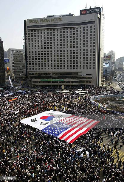 South Korean protesters carry huge US and South Korean flags during an antiNorth Korea rally in front of the Seoul City Hall March 1 2004 in Seoul...