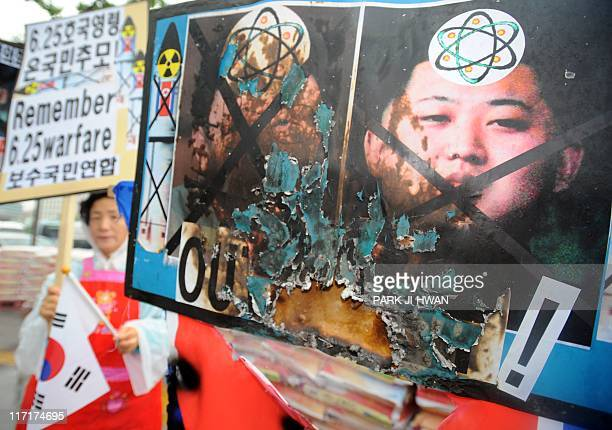 South Korean protesters hold placards and burnt portraits of North Korean leader Kim JongIl and his youngest son Kim JongUn during an antiNorth Korea...