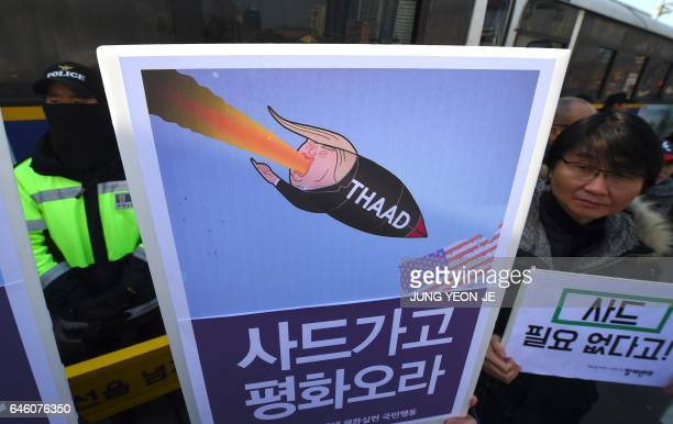 South Korean protesters hold placards showing a caricature of US President Donald Trump during a rally against the planned deployment of the USbuilt...