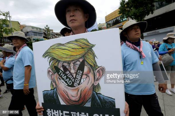 South Korean protesters holds a placard with an illustration of US President Donald Trump during a rally against the deployment of the Terminal...