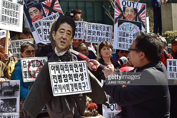 A South Korean protestor hits an effigy of Japan's Prime Minister Shinzo Abe with a saw during an antiJapan rally outside the Japanese embassy in...