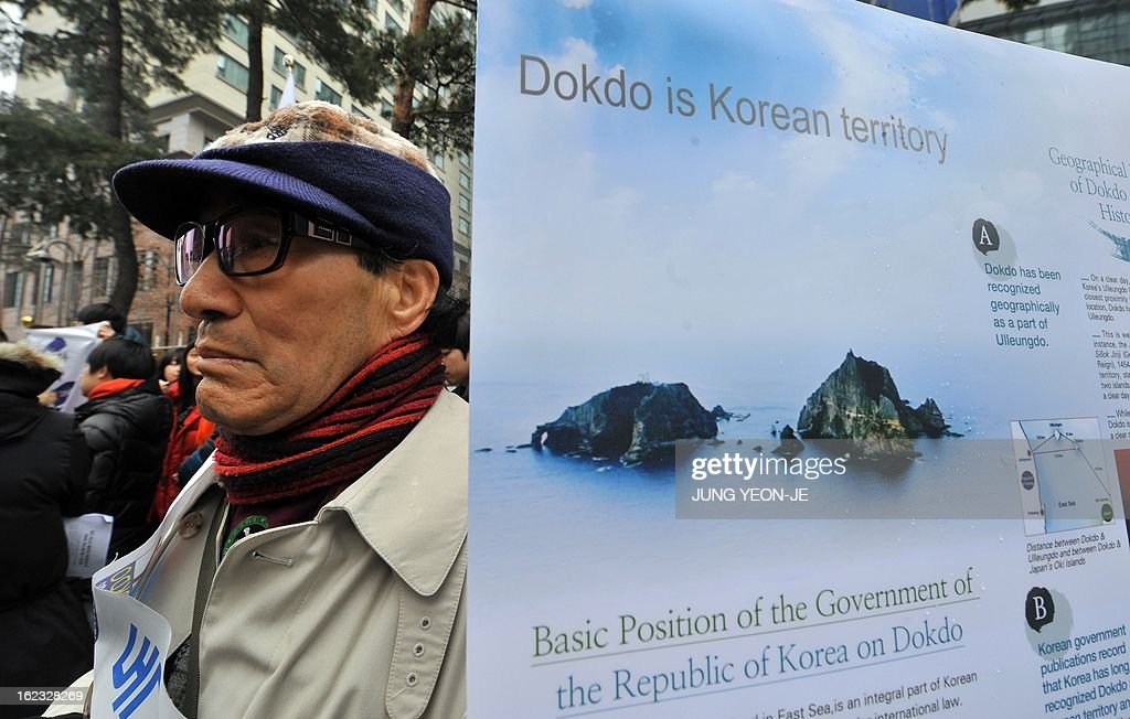 A South Korean protestor stands next to a placard reading 'Dokdo is Korean territory,' during an anti-Japan rally outside the Japanese embassy in Seoul on February 22, 2013 denouncing Japan's claims to the tiny chain of Seoul-controlled rocky islands, known as Dokdo in Korea and Takeshima in Japan. South Korea bashed Japan on February 22 for holding an annual rally to renew its claim to a set of tiny islands controlled by South Korea, which has been at the centre of a long-standing territorial feud.